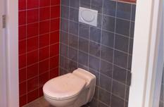 Toilet rood en grijs tegelwerk