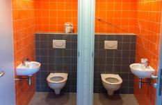 Toiletten oranje en grijs tegelwerk